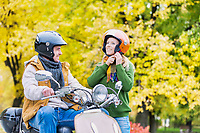 Portrait of beautiful woman putting her helmet on while husband is waiting to drive in park