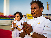 """22 FEBRUARY 2016 - KHLONG LUANG, PATHUM THANI, THAILAND:  People pray as monks file into the temple during Makha Bucha Day at Wat Phra Dhammakaya.  Makha Bucha Day is a public holiday in Cambodia, Laos, Myanmar and Thailand. Many people go to the temple to perform merit-making activities on Makha Bucha Day, which marks four important events in Buddhism: 1,250 disciples came to see the Buddha without being summoned, all of them were Arhantas, Enlightened Ones, and all were ordained by the Buddha himself. The Buddha gave those Arhantas the principles of Buddhism, called """"The ovadhapatimokha"""". Those principles are:  1) To cease from all evil, 2) To do what is good, 3) To cleanse one's mind. The Buddha delivered an important sermon on that day which laid down the principles of the Buddhist teachings. In Thailand, this teaching has been dubbed the """"Heart of Buddhism."""" Wat Phra Dhammakaya is the center of the Dhammakaya Movement, a Buddhist sect founded in the 1970s and led by Phra Dhammachayo.     PHOTO BY JACK KURTZ"""