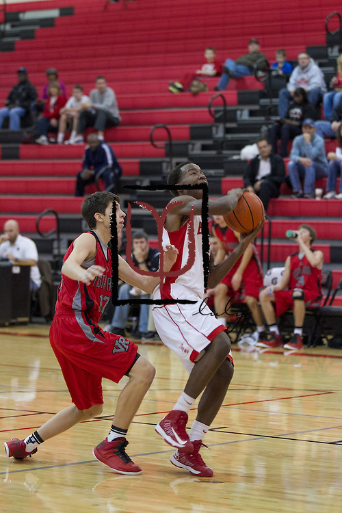 Belton's Thomas Barnes attempts a shot against Aiden Laurence and the Vista Ridge Rangers.  Vista Ridge beat Belton 63-46 at the Leander ISD Tournament held at Vista Ridge Gym Friday.