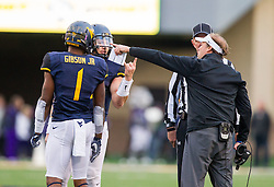 Oct 22, 2016; Morgantown, WV, USA; West Virginia Mountaineers quarterback Skyler Howard (3) and West Virginia Mountaineers head coach Dana Holgorsen and West Virginia Mountaineers wide receiver Shelton Gibson (1) talk to an official during the third quarter against the TCU Horned Frogs at Milan Puskar Stadium. Mandatory Credit: Ben Queen-USA TODAY Sports