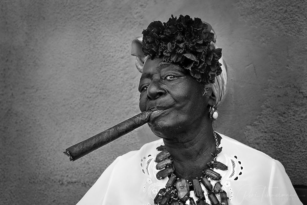 Various Cuban women pose for tourists while pretending to smoke a large Cuban cigar in the streets of Havana.