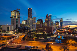 Vibrant Houston, Texas skyline at sunset with traffic motion blur and the downtown theater district in the foreground.