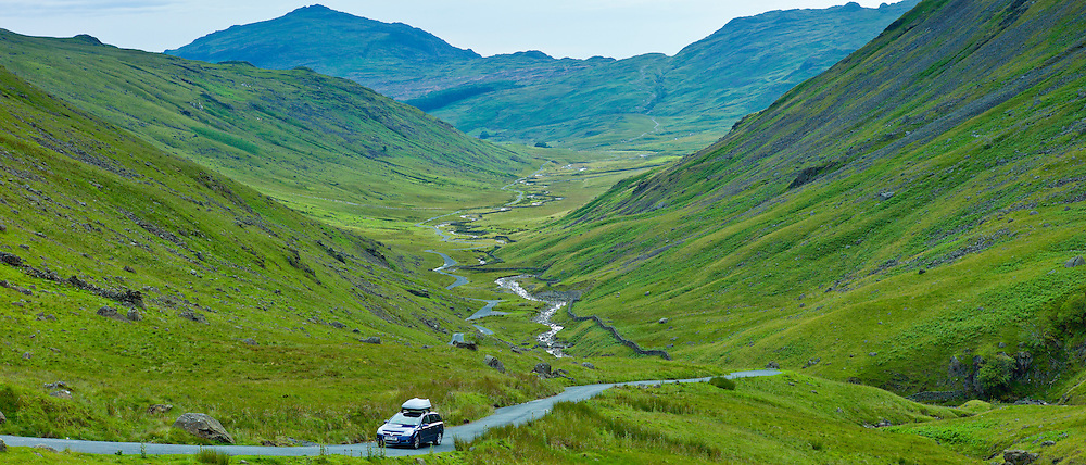 Tourist car on Langdale Pass surrounded by Langdale Pikes in the Lake District National Park, Cumbria, UK