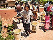 03 JUNE 2016 - SIEM REAP, CAMBODIA: A woman carries water to her home after her water jugs were filled at a water distribution point in Sot Nikum, a village northeast of Siem Reap. Wells in the village have been dry for more than three months because of the drought that is gripping most of Southeast Asia. People in the community rely on water they have to buy from water sellers or water brought in by NGOs. They were waiting for water brought in by truck from Siem Reap by Water on Wheels, a NGO in Siem Reap. Cambodia is in the second year of  a record shattering drought, brought on by climate change and the El Niño weather pattern. There is no water to irrigate the farm fields and many of the wells in the area have run dry.     PHOTO BY JACK KURTZ