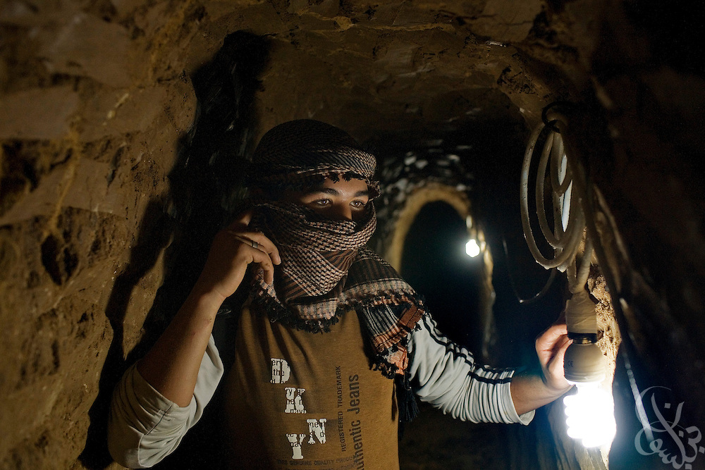 A Palestinian worker strings up light bulbs in a partially damaged smuggling tunnel on the Gaza-Egypt border in Rafah, Gaza January 22, 2009. Since the end of the 22 day Israeli military operation that included heavy airstrikes on the tunnel area, Palestinians have been busy reopening the undamaged tunnels, and rebuilding more heavily damaged or destroyed ones.  ..