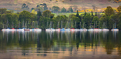 © Licensed to London News Pictures. 30/04/2019. Pooley Bridge UK. The moored boats of Ullswater Yacht Club reflect in the calm water of Ullswater lake near Pooley Bridge in Cumbria this morning. Photo credit: Andrew McCaren/LNP