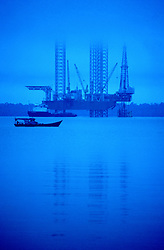 Malaysian river boat in the Straits of Malacca cruising past a jack-up offshore oil and gas drilling rig.