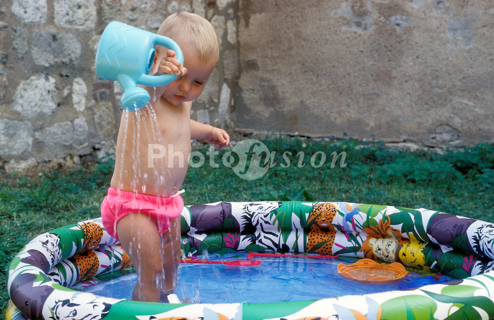 Baby girl playing in paddling pool UK