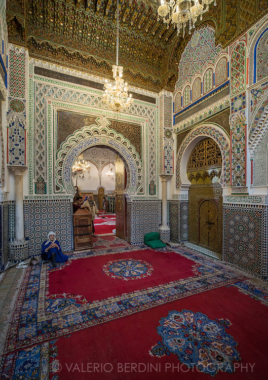 A woman sits at the entrance of Zaouia Moulay Idriss II. This mosque in Fez, Morocco, is dedicated to and is tomb of Moulay Idriss II, who ruled Morocco from 807 to 828 and founded the city of Fez for the second time in 810. Entrance to mosques in Morocco is forbidden to non muslims.