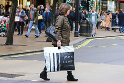 © Licensed to London News Pictures. 23/12/2018. London, UK. A woman with John Lewis shopping bag crosses the road. Last minute Christmas shoppers take advantage of pre-Christmas bargains in London's Oxford Street. Fewer shoppers have been reported shopping in Britain's high streets as online sales increase. Photo credit: Dinendra Haria/LNP