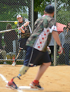 TELFORD, PA - MAY 24:  Wounded Warrior's Josh Wege (L) makes contact with the ball as William Wilk  (R) runs from first base during a Memorial Day weekend softball tournament featuring the Wounded Warrior Amputee Softball Team May 24, 2014 in Telford, Pennsylvania.  Wounded Warrior Amputee Softball Team (WWAST) is group of veterans and active-duty soldiers who lost limbs in Iraq and Afghanistan. They are able to compete at high levels by wearing prostheses that allow them to hit, run, catch and throw. This year is the team's three-year anniversary and have a winning record of 110-48 while playing in 28 states and 75 cities.  (Photo by William Thomas Cain/Cain Images)