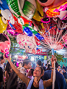 "27 NOVEMBER 2012 - BANGKOK, THAILAND:  A balloon vendor at the Wat Saket Temple Fair in Bangkok. Wat Saket, popularly known as the Golden Mount or ""Phu Khao Thong,"" is one of the most popular and oldest Buddhist temples in Bangkok. It dates to the Ayutthaya period (roughly 1350-1767 AD) and was renovated extensively when the Siamese fled Ayutthaya and established their new capitol in Bangkok. The temple holds an annual fair in November, the week of the full moon. It's one of the most popular temple fairs in Bangkok. The fair draws people from across Bangkok and spills out in the streets around the temple.   PHOTO BY JACK KURTZ"