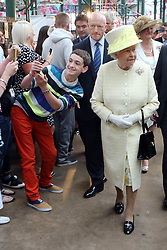Image ©Licensed to i-Images Picture Agency. 24/06/2014. Belfast, Northern Ireland. A young male tries to do a selfie with Britain's Queen Elizabeth as she tours St.Georges Market in Belfast,. The Queen is on a 3 day tour of Northern Ireland. Picture by Paul McErlane / i-Images
