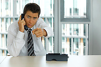 portrait of young confident caucasian businessman talking on phone