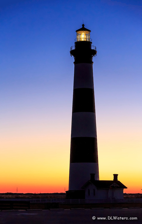 The first rays of warm orange light to peek over the horizon at Bodie Island Lighthouse.