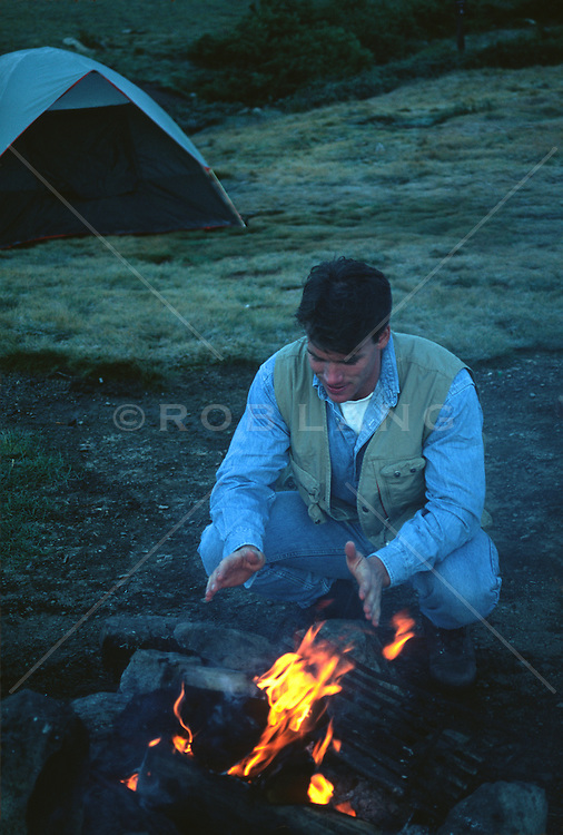 Man warming himself by a fire at a campsite