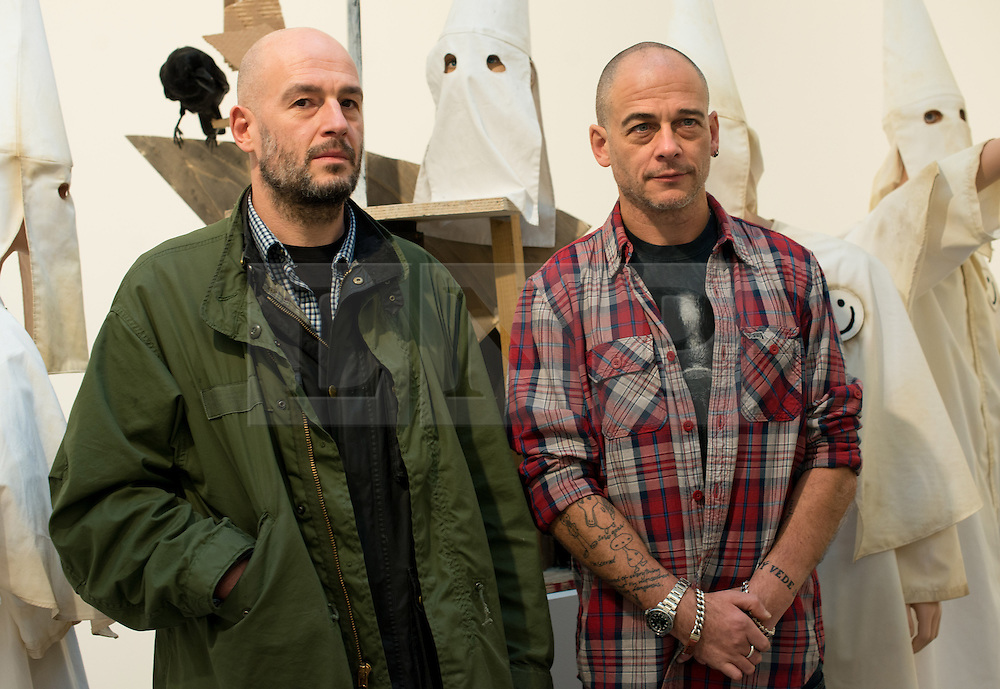 © Licensed to London News Pictures.27/11/2013. London, UK. Jake and Dinos Chapman (r) pose for photographers among artworks at Serpentine Gallery. Jake and Dinos Chapman create iconoclastic sculptures, installations and two-dimensional works that address a wide range of themes including morality, religion, history of art and consumer culture. The gallery launches its winter exhibitions that present Jake and Dinos Chapman: Come and See and Egyptian artist, Wael Shawky artworks.Photo credit : Peter Kollanyi/LNP
