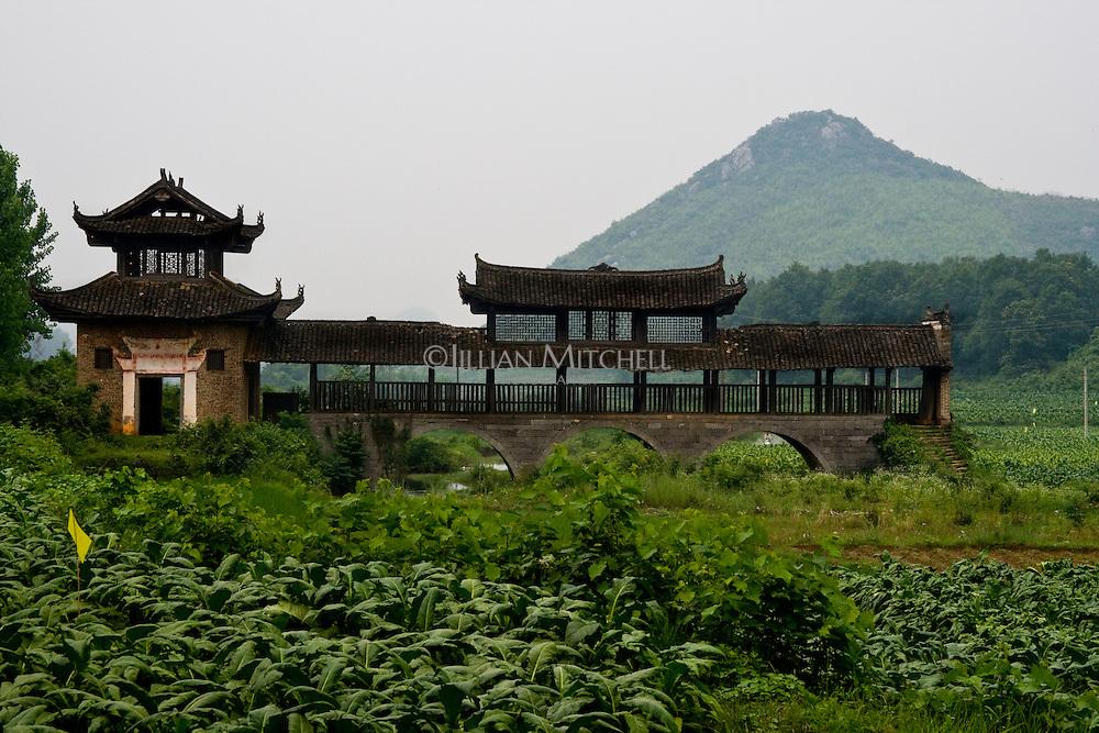 Old wind and rain bridge sitting in the fields in fuchuan yao autonomous region.