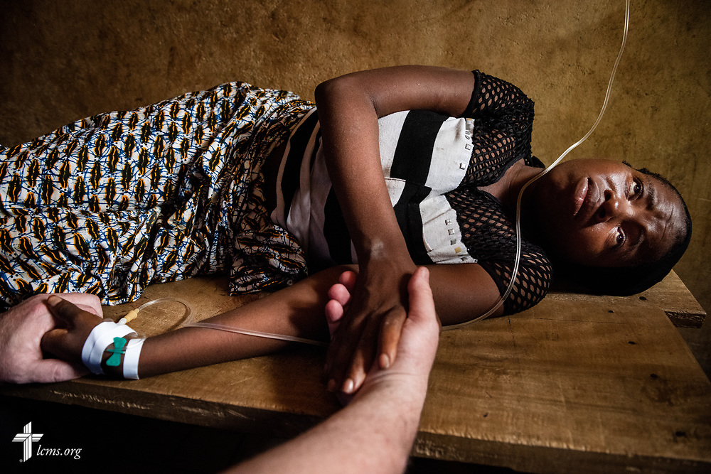 The Rev. Michael Awe, team leader and pastor at Hope Lutheran Church, South Sioux City, Neb., holds Fatmata's hands as she undergoes an IV on the fifth day of the LCMS Mercy Medical Team on Friday, May 11, 2018, in the Yardu village outside Koidu, Sierra Leone, West Africa. LCMS Communications/Erik M. Lunsford