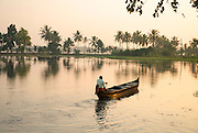 Man paddling a canoe at sunrise, Kerala Backwaters, India