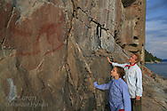 Mother and daughter admire centuries-old Ojibwe pictograph of mythological creatures, one of several story scenes that adorn Agawa Rock in Lake Superior Provincial Park, Ontario; Canada.