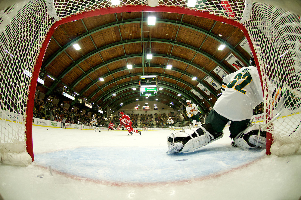 Terriers forward Wesley Myron (9) shoots the puck past Catamount goalie Billy Faust (32) for a goal during the mens hockey game between the Boston Terriers and the Vermont Catamounts at Gutterson Field House on Friday night November 16, 2012 in Burlington, Vermont.  The shot  by Myron shattered the front element of the goal camera.  If you look closely you can see the puck in the upper left hand side.