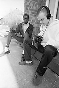Barry and Neville sat outside wearing headphones, High Wycombe, UK, 1980s.