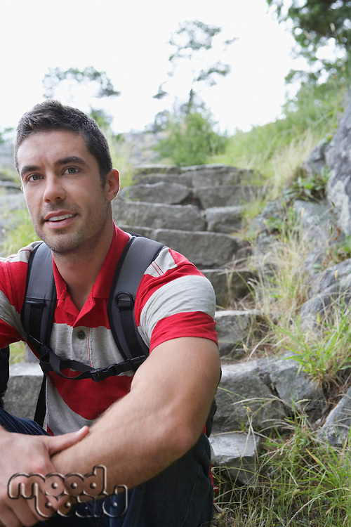 Man sitting on steps in countryside smiling portrait