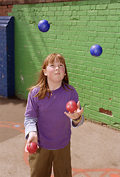 Young girl juggling balls,