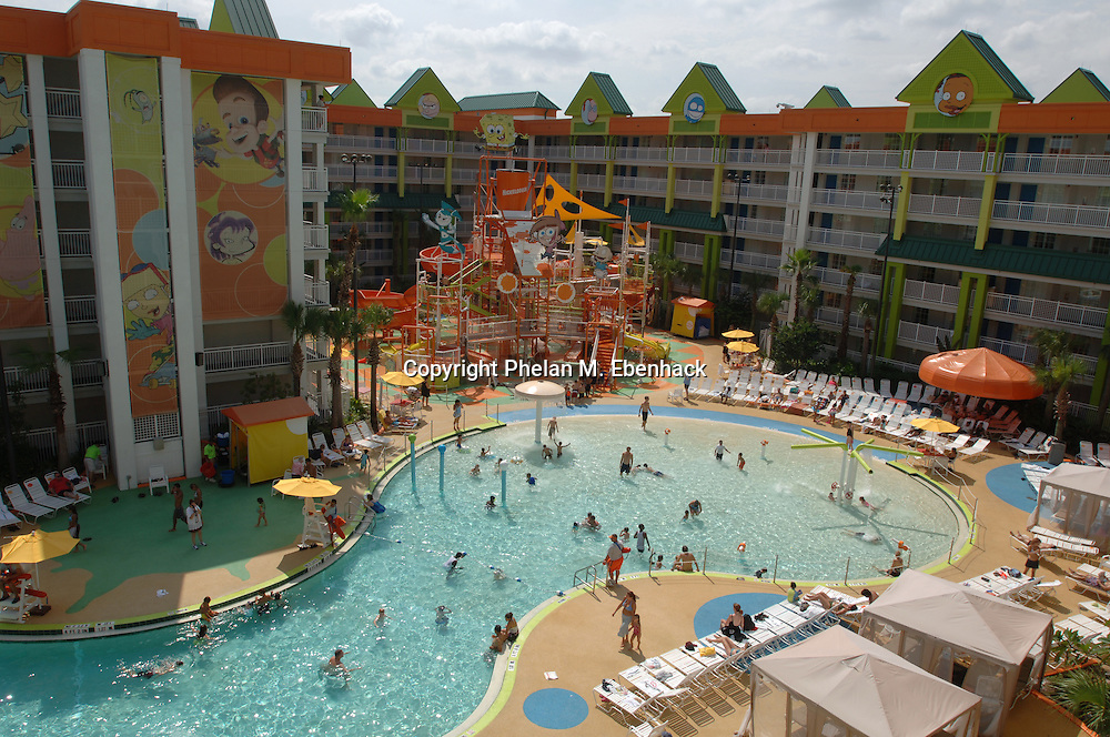 Families lounge around the winding pool at the Nickelodeon Family Suites by Holiday Inn hotel in Orlando, Florida.  This is a new concept combining the Nickelodeon name with a family-friendly designed hotel.