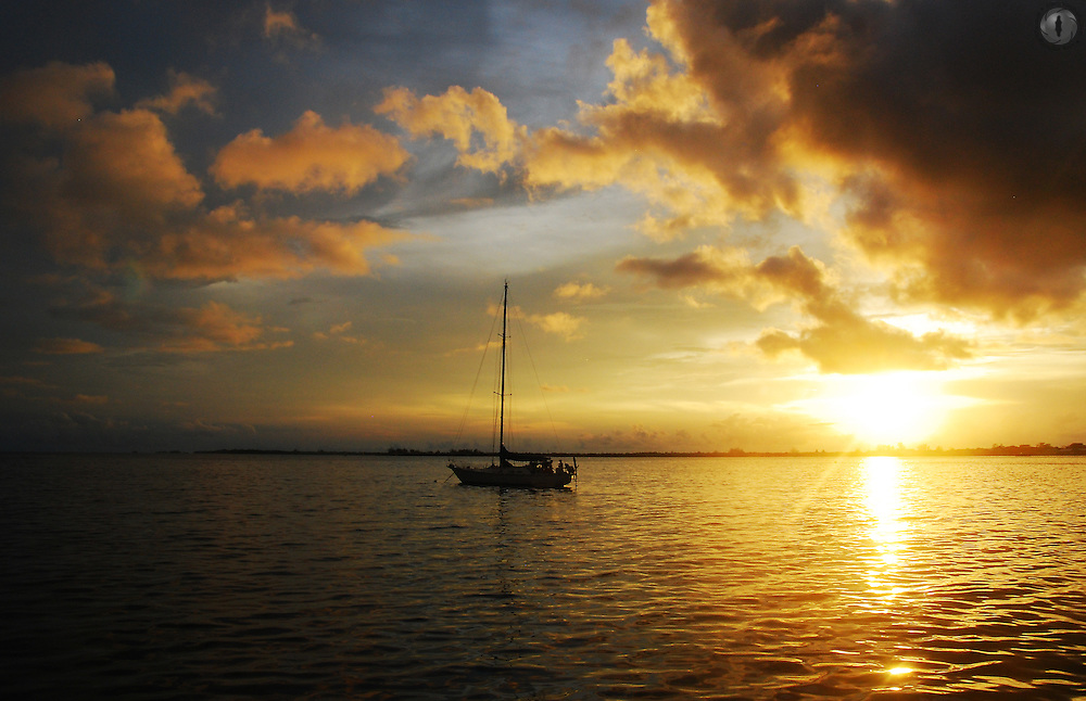 Sunset from Utila Island, off the coast of Honduras, with a sail boat silhouetted against the orange sky.