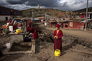 For a story by Ed Wong : CHINASICHUAN - Two journals in Sichuan<br /> Yarchen Gar, Sichuan, China<br /> October 11th, 2016<br /> A nun waiting to fill her bucket at a collective water tap. Thousands of nuns live in Yarchen Gar in poor sanitary conditions, with no running water, little or no electricity, in cramped makeshift houses.<br /> Gilles Sabri&eacute; for The New York Times