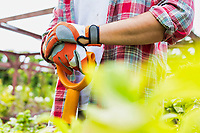 Close up of gardener wearing gloves while holding shovel in garden shop