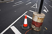 A newly-painted road surface reveals a new traffic cone alongside a temporary traffic light pole set in a drum of concrete.