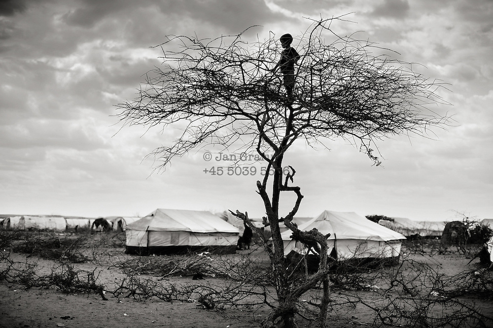 Dollo Ado, Ethiopia.October2011<br /> In the refugeecamp &quot; Hilaweyn&quot; also called &quot;Hells wind &quot; a small boy overlooks the massive camp which is now grown to more than 40.000 refugees... Refugees are still arriving in large numbers and due to that - relieforganisations have started to build a fifth camp in the area.<br /> Save the children  are working in all the camps, trying to improve the daily life for the many children in the camps.<br /> &rdquo; The drought in the horn of Africa is affecting more than 4.5 million people in Ethiopia. In addition, more than 140.000 refugees from Somalia have settled in camps in the border region between Somalia and Ethiopia. In the area around the border city Dollo Ado, four large refugee camps are already over crowded. A fifth camp is under construction due to the big influx still taking place. Many of the refugees are children, arriving severely malnutritioned. The mortality rate among small children has been brought down, but still children are dying on a daily basis...<br /> The four camps &ndash;Hilaweyn,Kobe, Malkadida and Bokomayo are now hosting more than 120.000 refugees and more are coming daily....