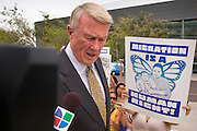 21 AUGUST 2012 - PHOENIX, AZ: JOHN J. BOUMA, chairman of Snell and Wilmer, the firm defending Arizona in the ongoing lawsuits surrounding SB 1070, talks to a reporter from UNIVISION while he walks past protesters after a hearing in Phoenix Wednesday. A handful of protesters waited outside the Sandra Day O'Connor Courthouse in Phoenix Wednesday while lawyers from the American Civil Liberties Union (ACLU) and Mexican American Legal Defense and Education Fund (MALDEF) sparred with lawyers from Maricopa County and the State of Arizona over the constitutionality of section 2B of SB 1070, Arizona's tough anti-immigrant law. Most of the law was struck down by the US Supreme Court in June, but the Justices let section 2B stand pending further review. The suit is being heard in District  Judge Susan Bolton's court. It was Judge Bolton who originally struck down SB 1070 in 2010. A ruling is expected later in the year.   PHOTO BY JACK KURTZ