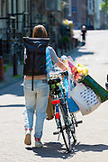 Woman with heavy load on bicycle by Brouwersgracht and Herengracht, Amsterdam, Holland