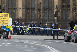 London, March 22nd 2017. Police move to their positions in the aftermath of a shooting incident on Westminster Bridge, where several pedestrians were also mown down by a car.