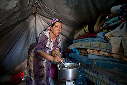 © Licensed to London News Pictures. 12/05/2013. Dohuk, Iraq. Hadia Oso Dawed (40), a Syrian refugee, makes lunch for her family inside her tent at a refugee camp in Iraqi-Kurdistan, set up for Syrians escaping the ongoing civil war. The camp, close to the city of Dohuk, now houses in the region of 45,000 refugees, with around 400 new arrivals every day. Photo credit: Matt Cetti-Roberts/LNP