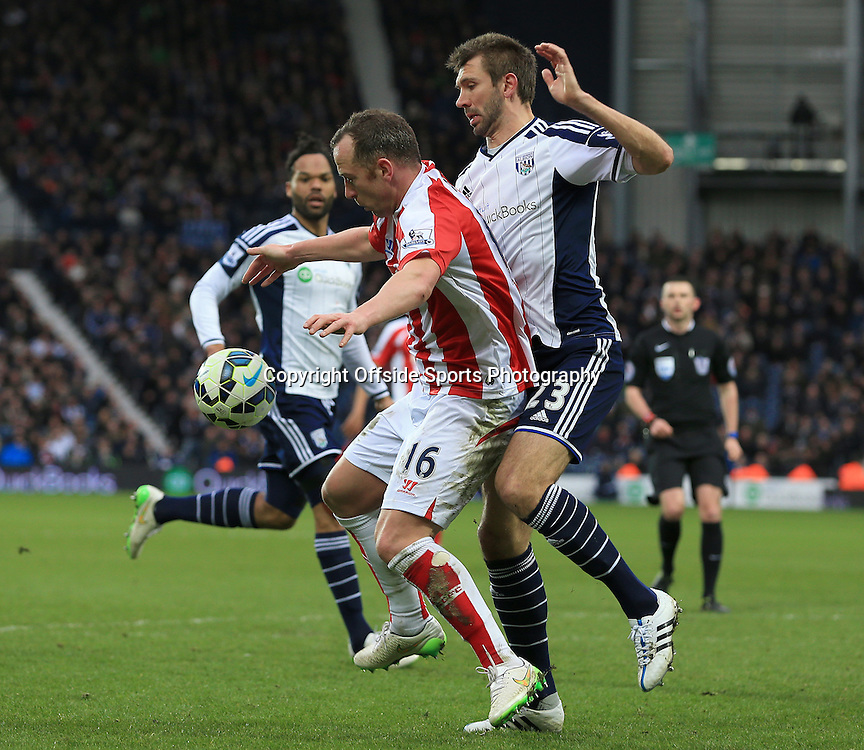 14th March 2015 - Barclays Premier League - West Bromwich Albion v Stoke City - Charlie Adam of Stoke City controls the ball under pressure from Gareth McAuley of West Bromwich Albion - Photo: Paul Roberts / Offside.
