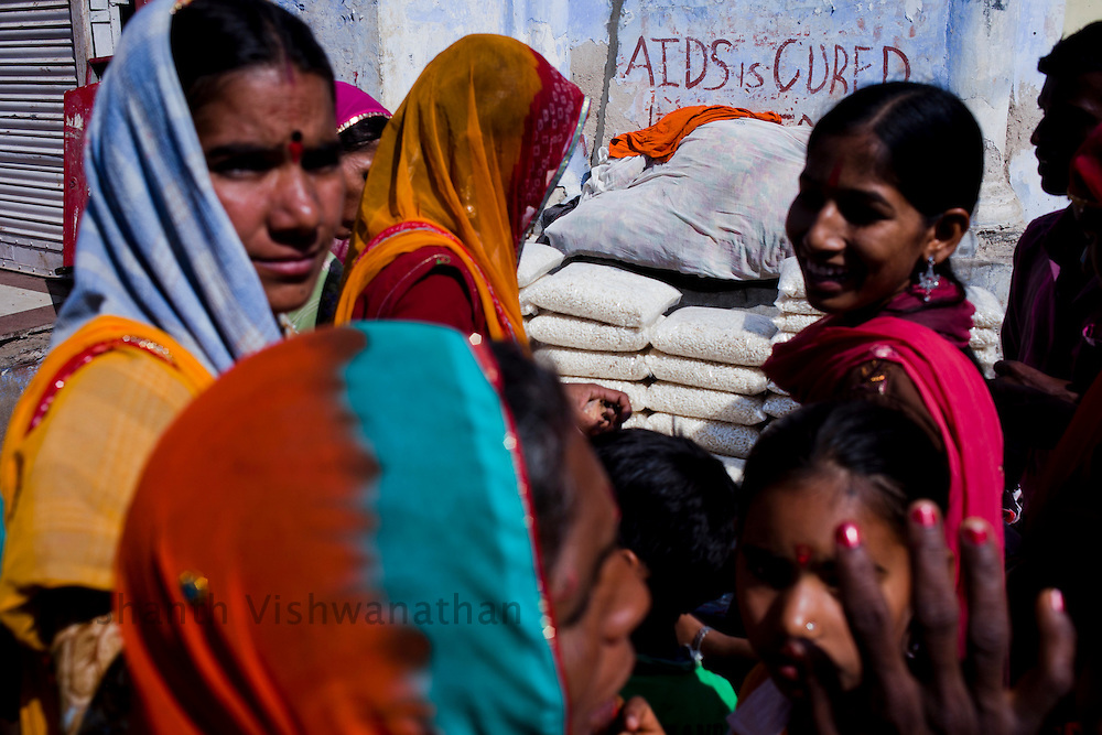"Women react as they shop next to a street graffitti proclaiming ""Aids is Cured"" near the Bramha temple  in Pushkar, India, November 3, 2011.  Photographer: Prashanth Vishwanathan"