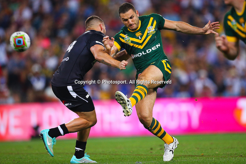 Robbie Farah kicks ahead as Dean Whare tackles during the Four Nations test match between Australia and New Zealand at Suncorp Stadium,  Brisbane Australia on October 25, 2014.