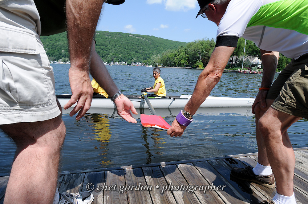 GREENWOOD LAKE, NY.  An all-woman team of rowers is pushed away from a dock by two rowing coaches prior to their race during the 15th. Annual Greenwood Lake Spring Regatta in Greenwood Lake, NY on Sunday, June 2, 2013.   © Chet Gordon/THE IMAGE WORKS