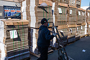 Brooklyn, NY - 26 March 2020. Residents of New York City have been asked to stay home as a result of the novel coronavirus, and all but essential businesses have been asked to close. In Brooklyn's Midwood neighborhood, many businesses have their shutters rolled down, and the few that are open limit the number of people who can enter. Corrugated cartons for home delivery of groceries are stacked in tall piles in front of Blue Ribbon Groceries on Avenue J.
