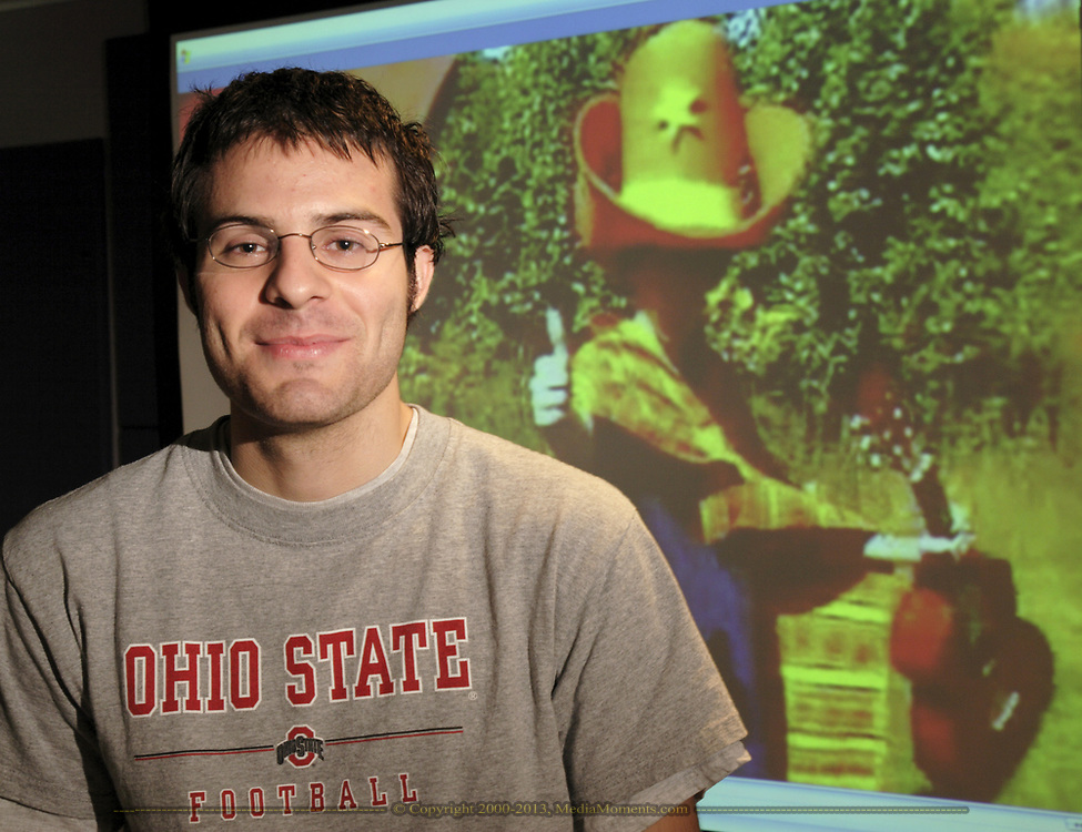 """Garrett Senney stands in front of the big screen TV displaying his video """"Sancho,"""" which won a Hometown Video Award.  Senney says he had the finished video, which he did for a class project, a week after began filming.  He originally entered it in the Hometown Video contest because he felt it would be """"nice to get feedback"""" about the video."""