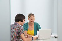 Two women working at laptop in office smiling