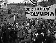 "Irish Theatre Industry Protest at Leinster House.1983.07.12.1983.12.07.1983.7th December 1983...With the imposition of a 23% V.A.T.rate on theatre tickets, the theatre industry was feeling the strain. Maureen potter and Brendan Grace aka ""Bottler"" led the protest to the gates of Leinster House Dublin.. .Image of the protesters as the listen to Speeches from the podium. .A touch of fun is brought to proceedings as spelling on Olympia Theatre banner is wrong."