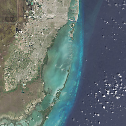 Many national parks in the United States can be experienced by driving scenic roads or hiking on trails. Visit Biscayne National Park in southern Florida, however, and you might want to explore by boat; 95 percent of this park is under water.<br /> On February 25, 2016, the Operational Land Imager (OLI) on the Landsat 8 satellite acquired this natural-color image of Biscayne National Park. The park encompasses the northernmost Florida Keys, starting from Miami to just north of Key Largo.<br /> The keys run like a spine through the center of the park, with Biscayne Bay to the west and the Atlantic Ocean to the east. The water-covered areas span more than 660 square kilometers (250 square miles) of the park, making it the largest marine park in the U.S. National Park System. Biscayne protects the longest stretch of mangrove forest on the U.S. East Coast, and one of the most extensive stretches of coral reef in the world.<br /> acquired February 25, 2016<br /> acquired July 10 -<br /> 14, 2001<br /> download large image (21 MB, JPEG, 10000x18000)<br /> acquired July 10 -<br /> 14, 2001<br /> download<br /> GeoTIFF file (21 MB, TIFF, 10000x18000)<br /> Some of what lies below those waters is visible in data acquired by the Experimental Advanced Airborne Research Lidar (EAARL). EAARL's Lidar measured the time it took for a pulse of light to go from the aircraft, through the water, reflect off the seafloor, and back to the airplane. Researchers can convert that travel time into measurements of height, and map the underwater topography. According to C. Wayne Wright, a remote-sensing scientist who worked at NASA's Wallops Flight Facility, EAARL was designed and built by NASA specifically to get a high-resolution look at coral reef environments.<br /> The highlighted area in the second image above shows where EAARL acquired data in Biscayne National Park from July 10–14, 2001. The third image shows a detailed view of the center of the study area. White and light blue are the shallowest areas, primarily marking the location of coral reefs. Some