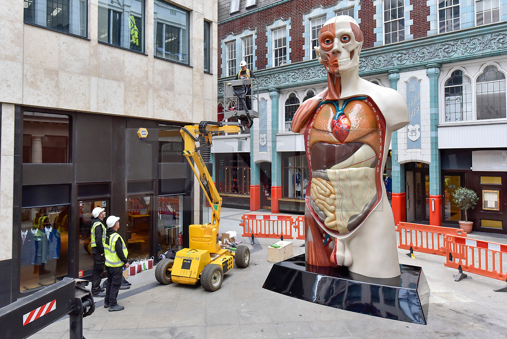 """© Licensed to London News Pictures. 24/06/2017. London, UK. Workmen unveil a 21 feet tall, 2.5 tonne bronze sculpture called """"Temple"""" by Damien Hirst near the Lloyds Building in the City of London.  The artwork will be on display as part of """"Sculpture in the City"""", a festival of sculpture in the City of London showing works by leading artists. Photo credit : Stephen Chung/LNP"""