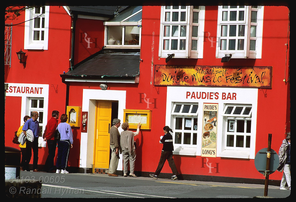 Couples stop to read menu outside Paudie's Bar in the town of Dingle, Ireland.